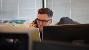 Salesperson speaking on phone behind computer